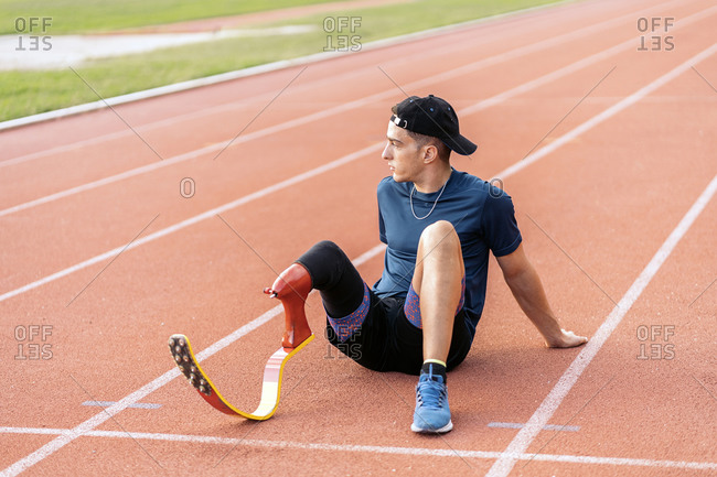 Disabled male athlete taking a break on a running track