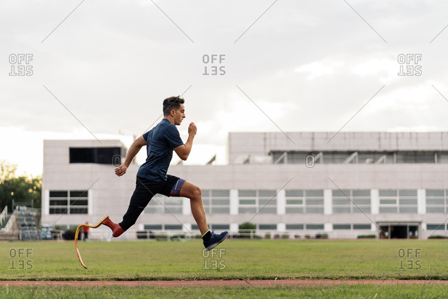 Determined young athlete with leg prosthesis training on a running track