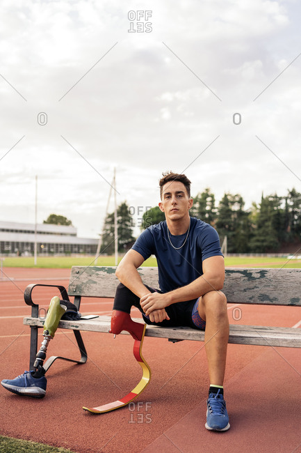 Young male athlete with a leg prosthesis sitting in a bench and looking at camera
