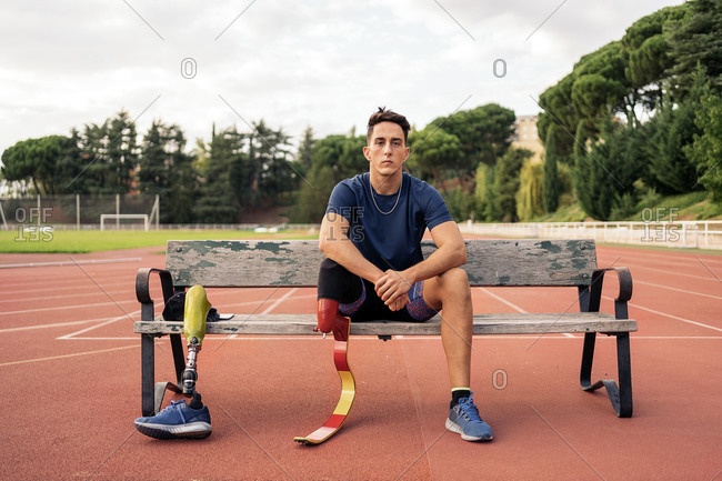 Portrait of a young male athlete with a leg prosthesis sitting in a bench and looking at camera