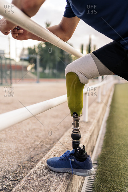 Close up disabled male athlete with leg prosthesis leaning on railing