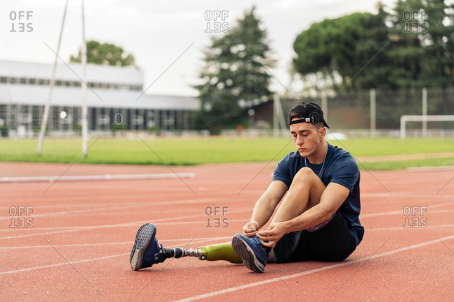 A young disabled male athlete taking a break and tying his running shoes
