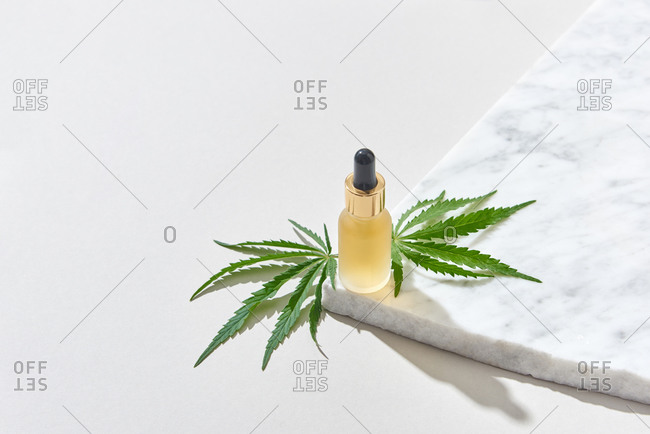 Bottle of essential cbd oil with green cannabis leaf.