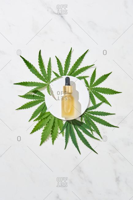 Round frame with CBD cannabis oil and marijuana leaves.