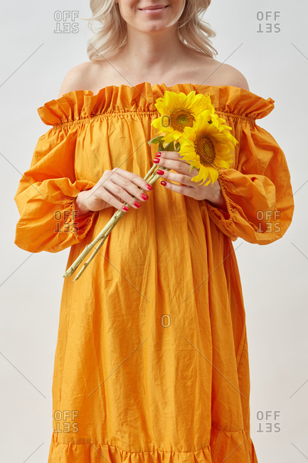 Pregnant young woman with beautiful yellow sunflowers.