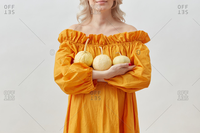 Smiling pregnant woman holds tree natural pumpkins.