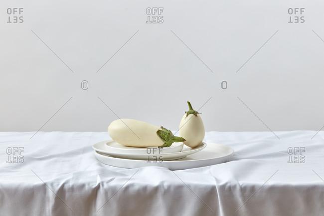 Fresh natural ripe white eggplant on a ceramic plates.