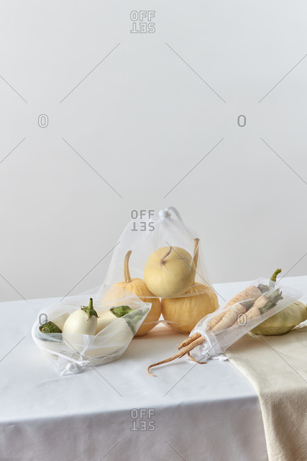 Reusable shopping meshes with assortment of vegetables.