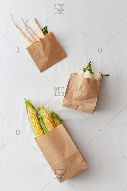 Paper eco bags with organic vegetables and roots.