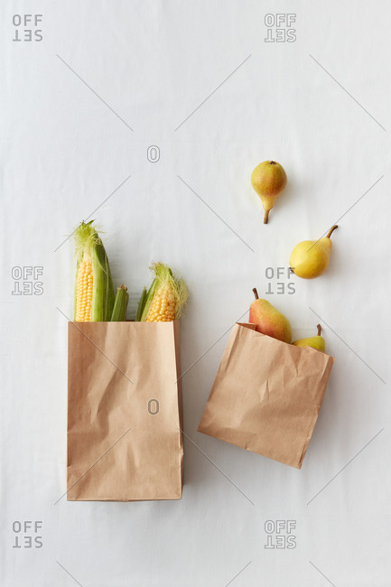 Two paper bags with organic natural corn and pears.