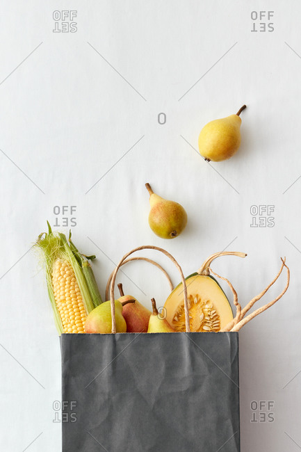 Paper bag with various fresh vegetables and fruits.