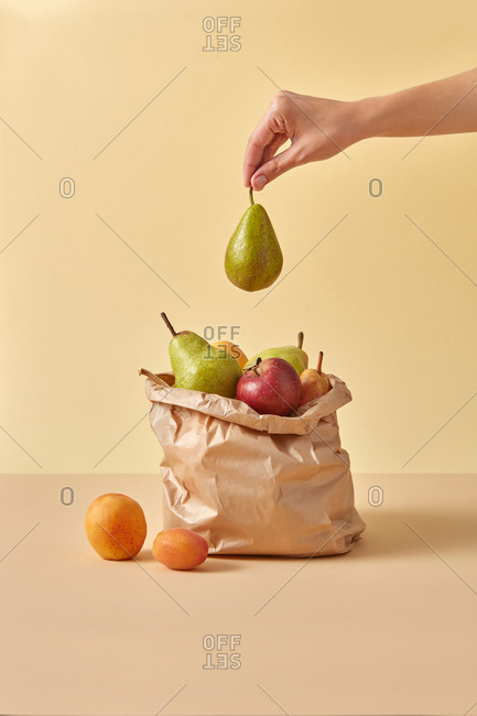 Woman hand puts ripe pear into paper bag with fruits.