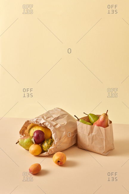 Two paper eco bags with fresh vegetables and fruits.