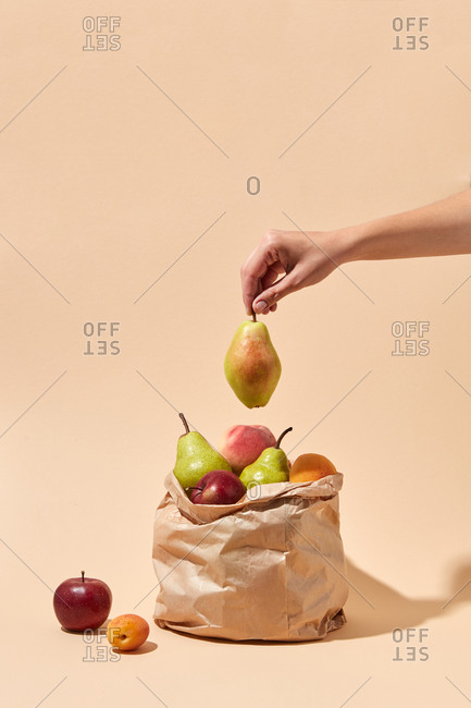 Woman's hand puts fresh pear into bag with fruits.