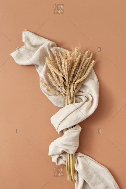 Natural linen textile towel with bunch of dry wheat.