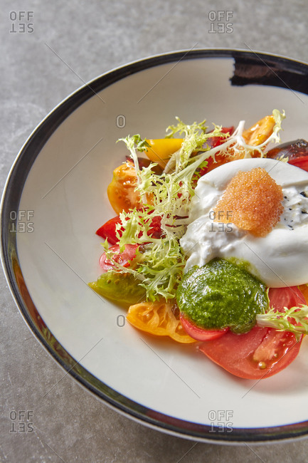 Salad from burrata cheese with tomatoes and pike caviar.