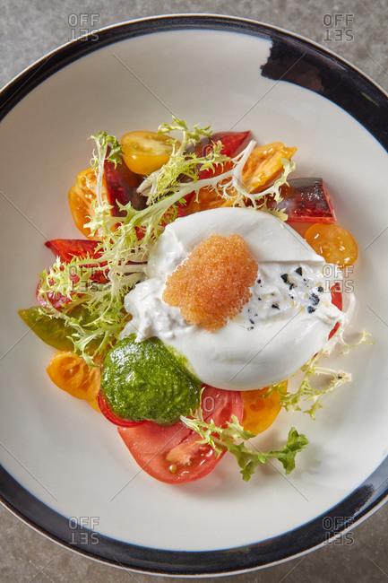 Fresh natural cheese burrata with salad and pike caviar.