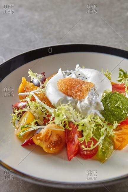 Salad from burrata, organic tomatoes and pike caviar.