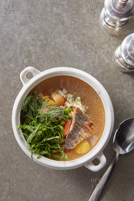Fish soup with vegetables and fresh greenery.