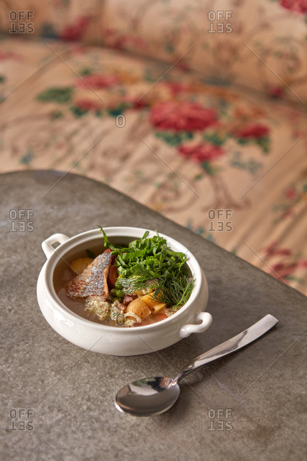 Freshly cooked fish soup with greenery and vegetables.