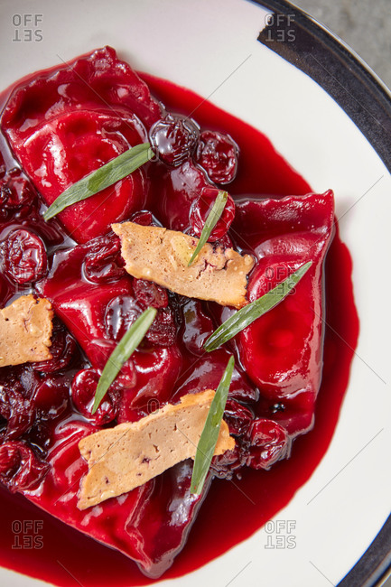 Close up sweet dumplings with cherry sauce and ricotta.