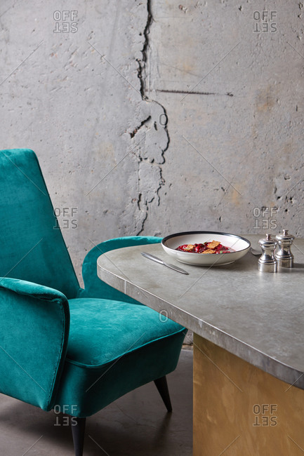 Served dinner table with chair on grey wall background.