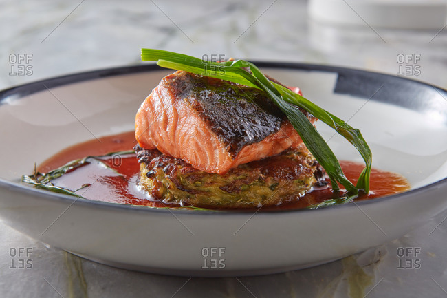 Natural grilled salmon with zucchini pancake and sauce.
