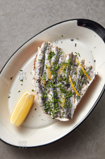 Fish snack from fresh anchovies on a bread with lemon.