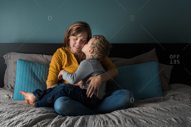 Boy sitting on mother's lap and kissing her cheek