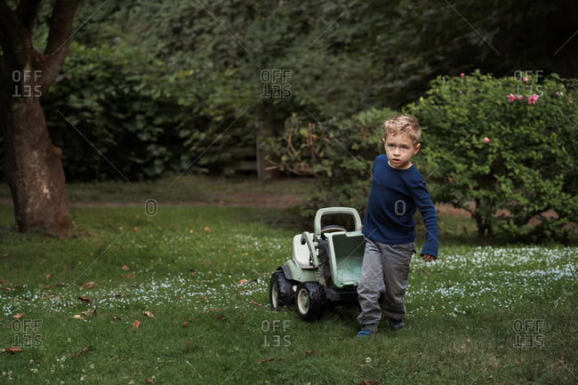 Child pulling a ride-on tractor through the yard