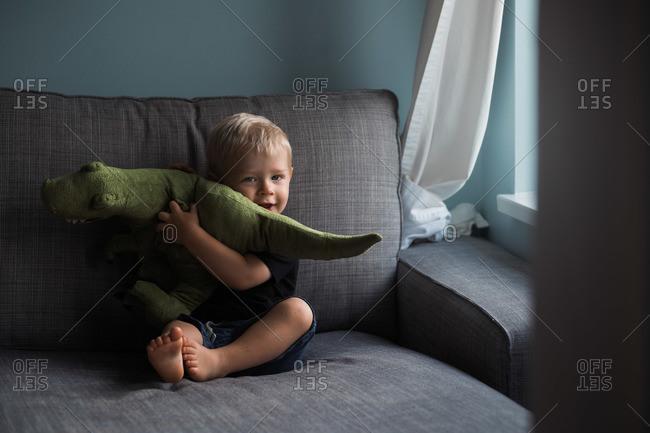 Toddler boy cuddling with a stuffed dinosaur