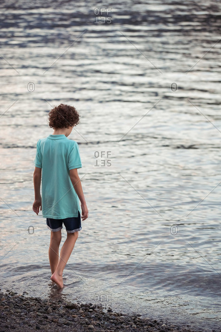 Boy wading in the waters at Barnet Marine Park in British Columbia, Canada