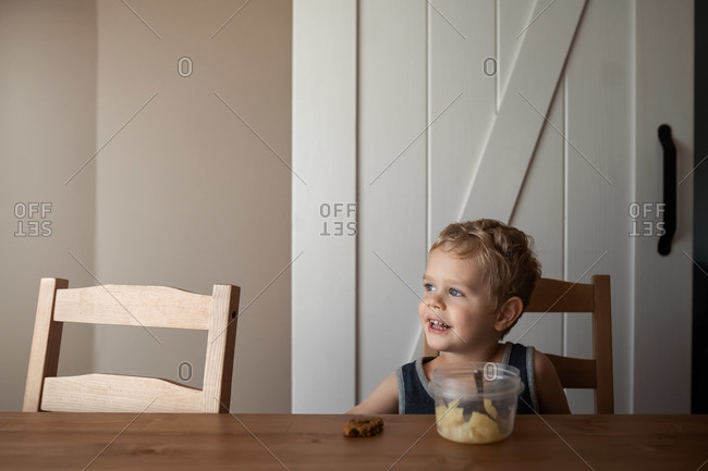 Toddler boy eating snack at the dining room table