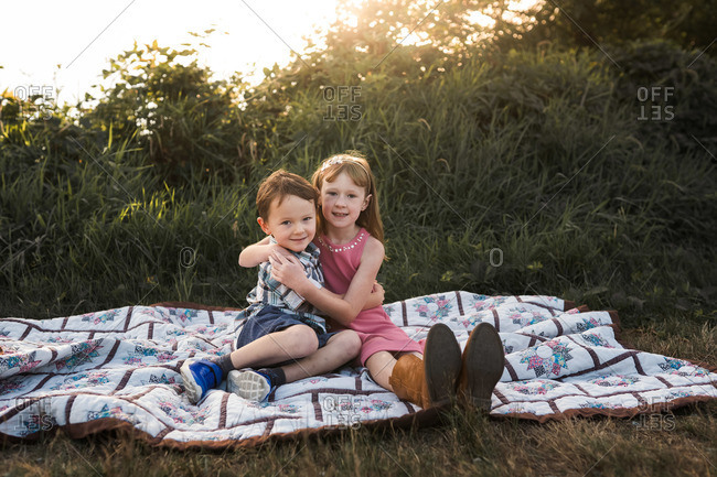 Brother and sister sitting on a picnic blanket at sunset