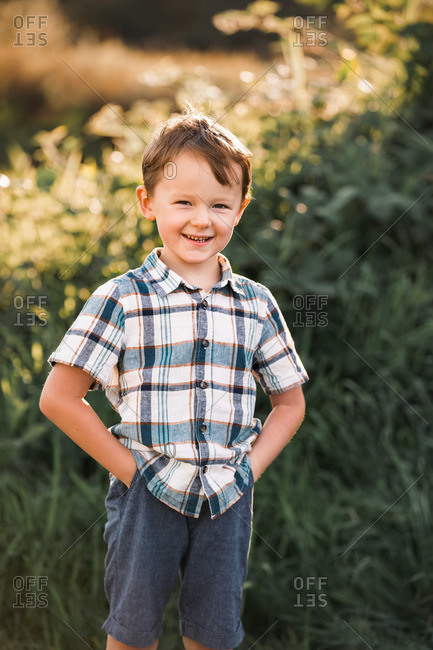 Portrait of a young boy wearing a plaid shirt with hands in his pockets at sunset