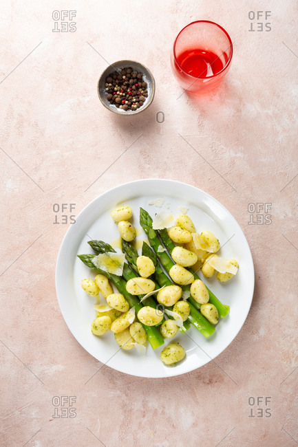 Potato gnocchi with spring asparagus on pink surface