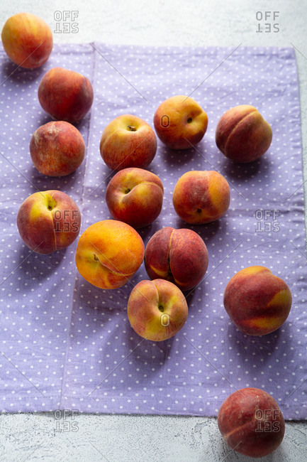 Fresh peaches on a purple polka dots textile