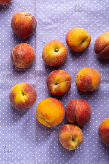 Overhead view of peaches on polka dots cloth