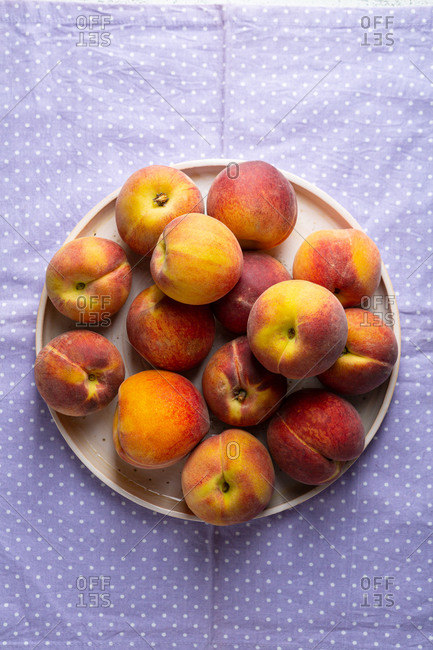 Overhead view of peaches on plate polka dots cloth
