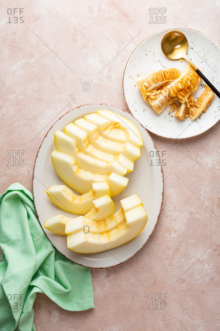 Overhead view of sliced melons on white platter