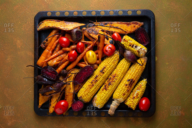 Overhead view of roasted roots and corn on the cob on baking sheet