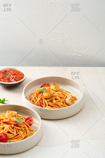 Spaghetti in two bowl on stone table