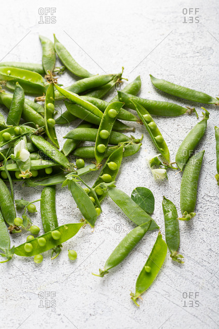 Pile of green peas and pods on white surface