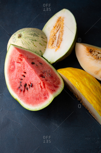 Close up of a variety of halved melons on dark surface
