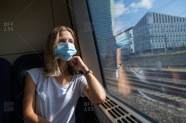 Woman sitting on train wearing a facemask during the Covid- 19 outbreak
