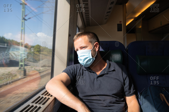 Man sitting on train wearing a facemask during the Covid- 19 outbreak