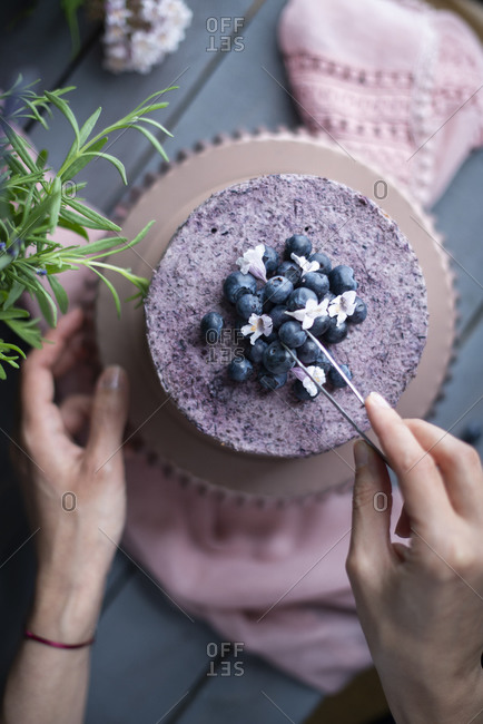Overhead view of a baker topping a layer cake with mousse, fresh blueberries and flowers
