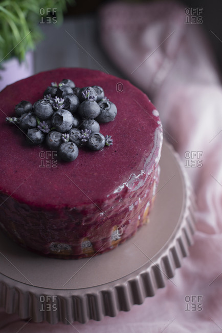 Layer cake with fresh blueberries, glazing, and lavender flowers