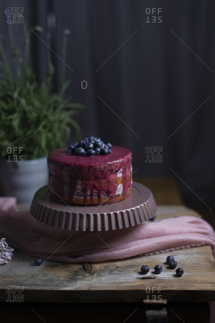 A purple glazed layer cake with fresh blueberries and lavender flowers