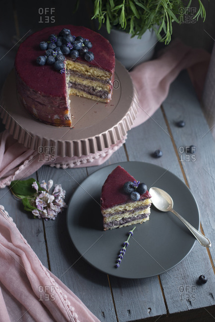 Overhead view of a layered cake with fresh blueberries, glazing, and lavender flowers being sliced and served